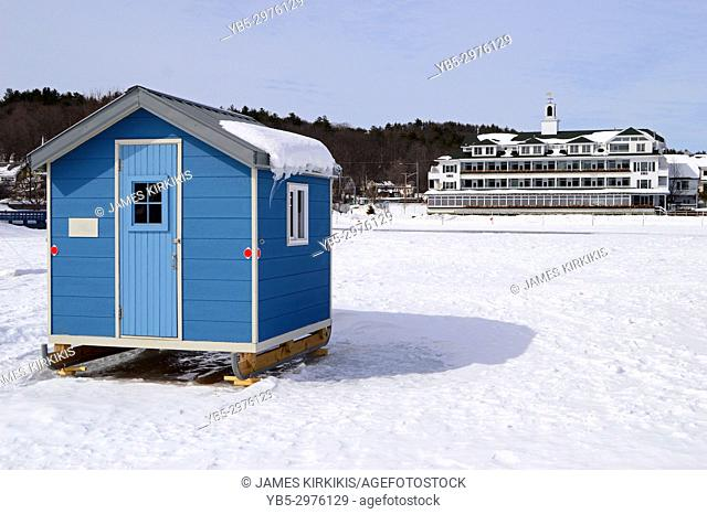A small ice fishing shelter is dwarfed by the larger Bay Point Inn on Lake Winnipesaukee New Hampshire