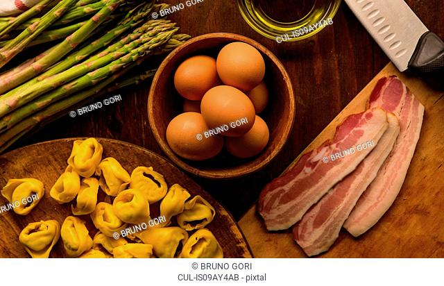 Overhead view of raw and prepared food, pasta, eggs and asparagus
