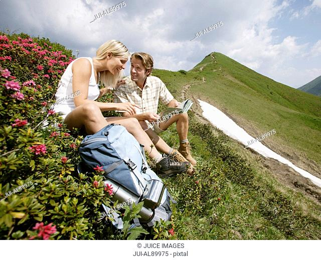 Couple sitting on mountain side, Kleinwalsertal, Allgau, Germany