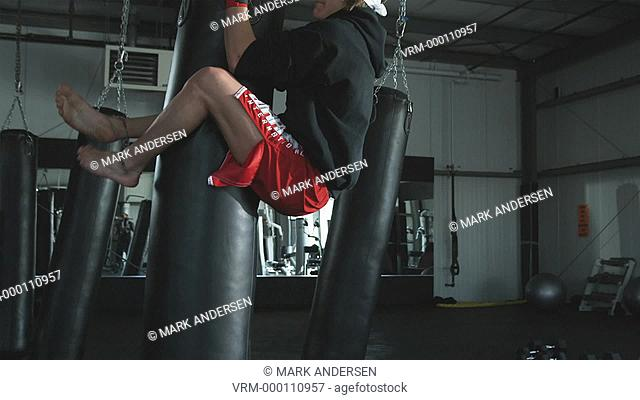 man jumping onto a punching bag and doing vertical sit ups to train