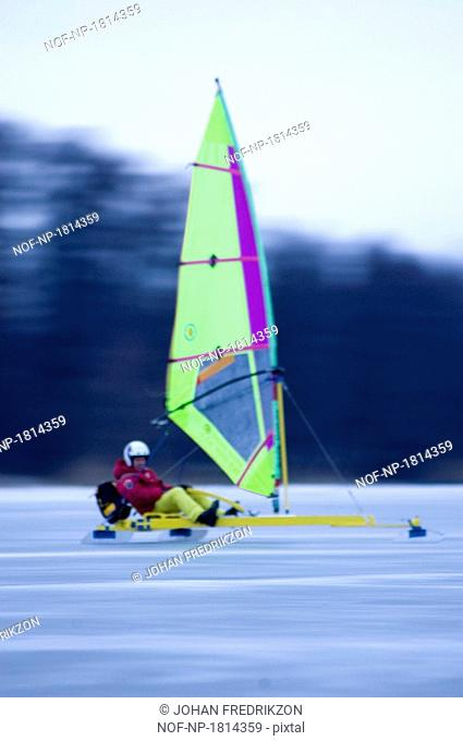 Side profile of a man sailing a boat on a frozen lake