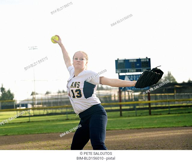 Caucasian softball player pitching ball in field