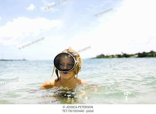 Boy (8-9) wearing swimming goggles standing in sea