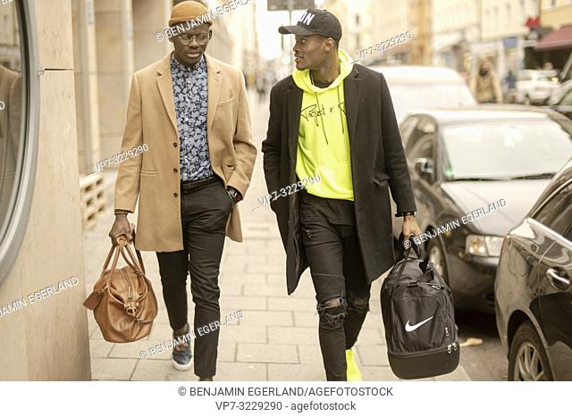 two stylish men walking together at pavement in city, male friends, in Munich, Germany
