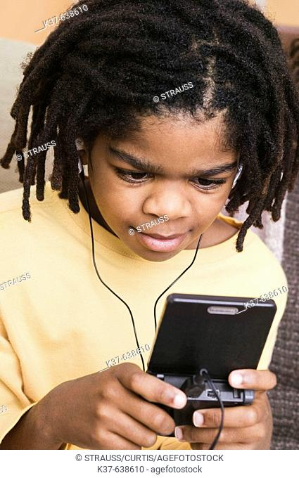African-American boy playing on gameboy at home