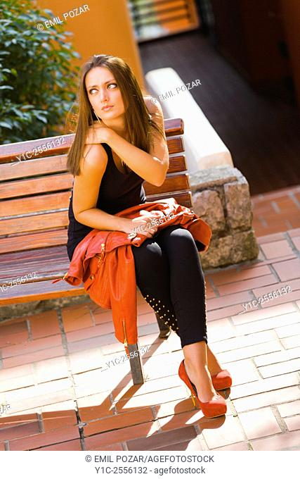 Beautiful young lady on wooden bench waiting for date