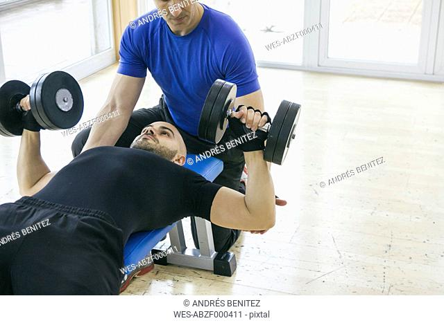 Man lifting weights assisted by a coach lying on a bench gym