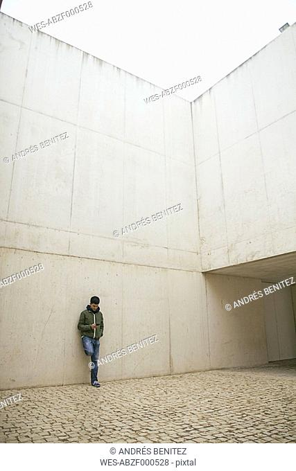 Man leaning against concrete wall looking at his smartphone