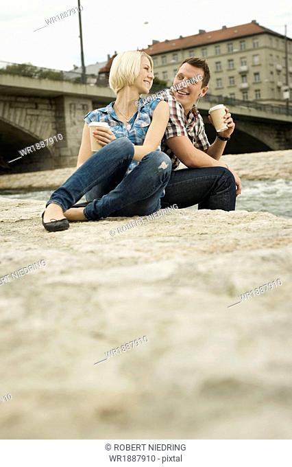 Young couple having a cup of coffee outdoors, Munich, Bavaria, Germany