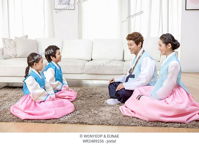 Side view of Korean family in traditional Korean clothes sitting face to face on a carpet