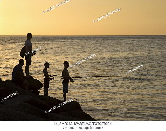 Man and boys fishing in Gulf of Mexico off North Jetty in Nokomis Florida against a orange sunset sky
