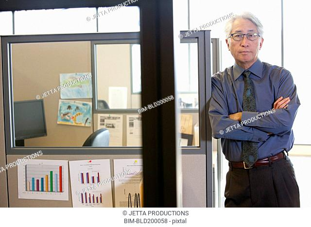 Asian businessman leaning on office cubicle