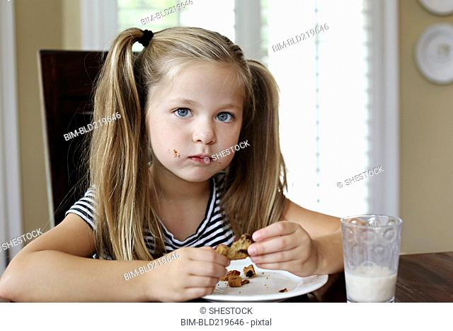 Girl eating cookie on table