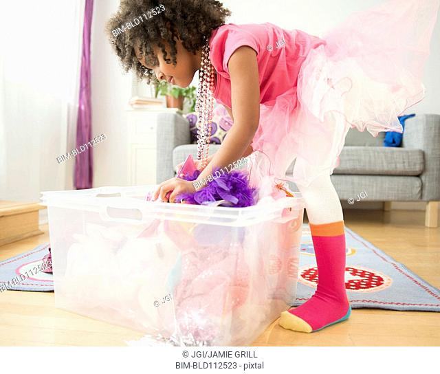 African American girl digging in clothes bin