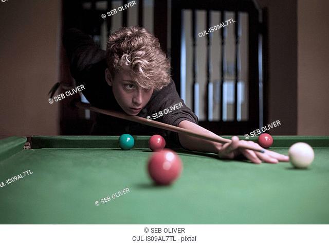 Teenage boy playing snooker