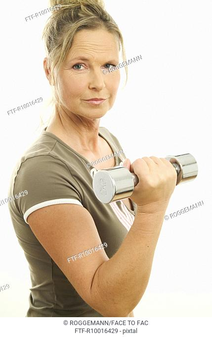 A senior woman holds the dumbbell weighing 2 Kg as she smiles at the camera