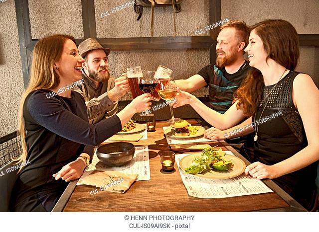Friends toasting at hipster bar