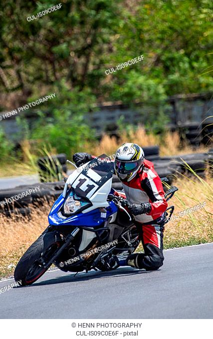 Male motorcyclist leaning sideways riding his motorbike on race track, Bangkok