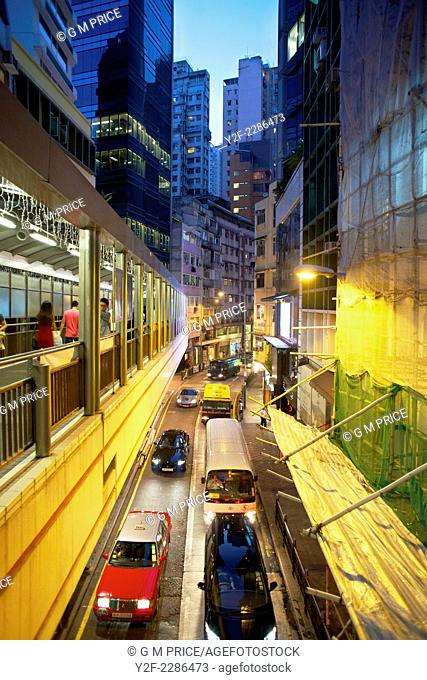 pedestrians use elevated walkway over traffic through Soho district at dusk, Hong Kong