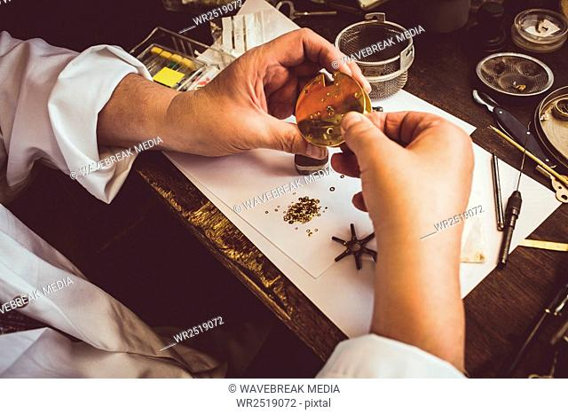 Hands of horologist repairing a watch