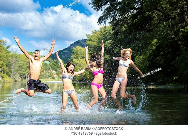 Group of teenagers having summer fun while jumping out of the water