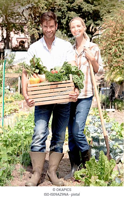 Portrait of mature couple in garden, holding crate of fresh vegetables