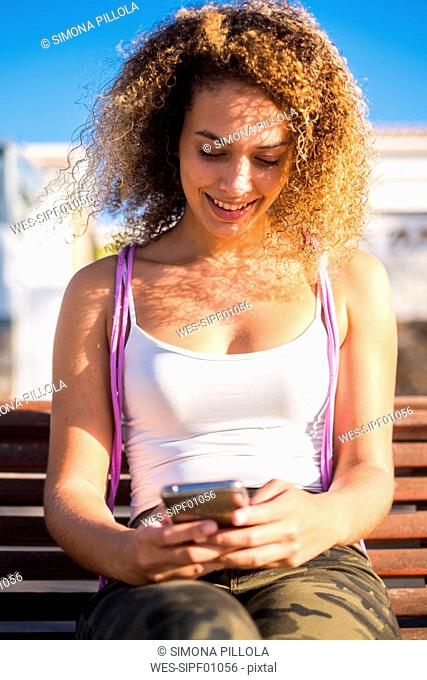 Smiling young woman sitting on bench looking at smartphone