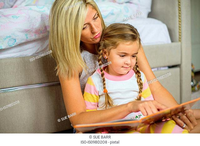 Mid adult woman sitting on floor reading with daughter