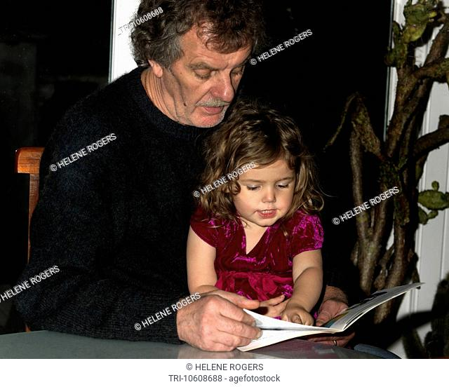Grandfather Reading Story to two Year Old Grand daughter