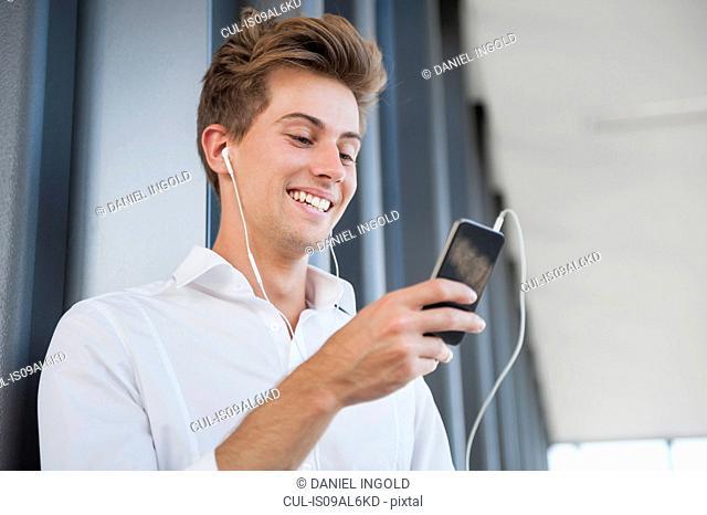 Young businessman wearing earphones