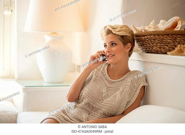 Woman talking on cell phone on sofa