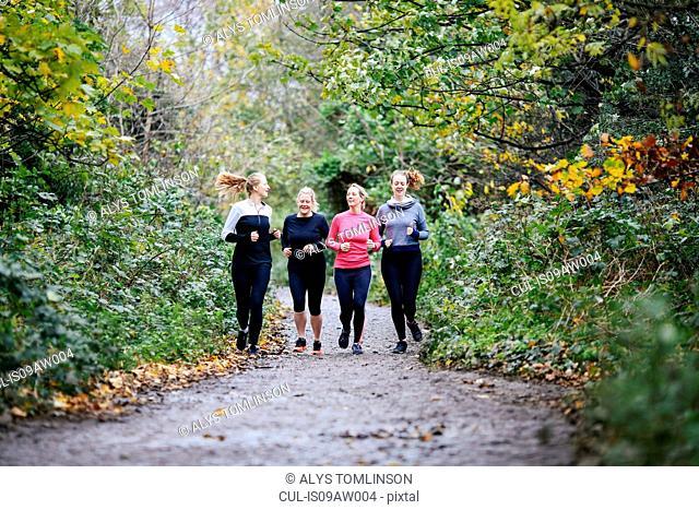 Teenage girl and women runners running in park