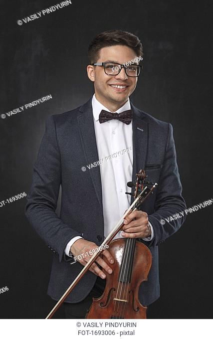 Portrait of smiling young man holding violin while standing against black background