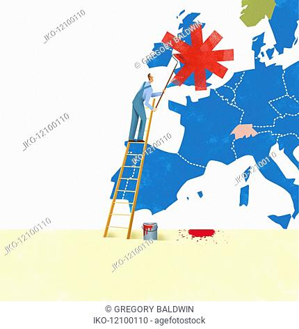 Workman painting over the United Kingdom on map of the European Union