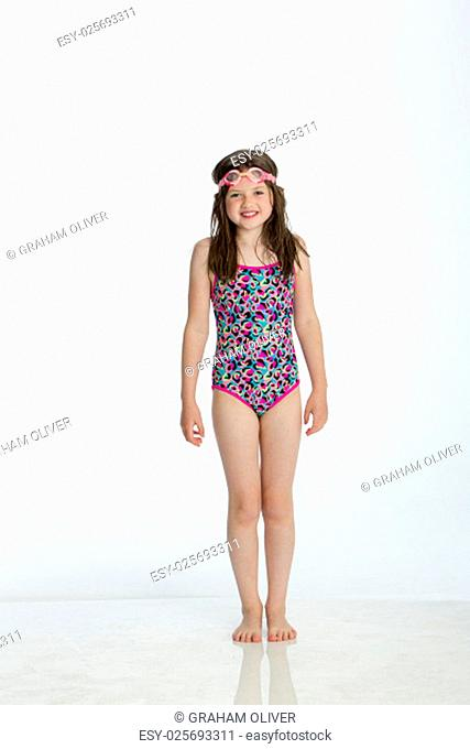 Full length shot of a little girl wearing a swimming costume with goggles on her head. She is smiling at the camera and standing against a white background
