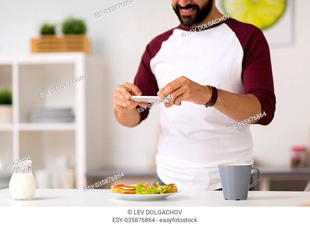 food, healthy eating and people concept - man with smartphone having breakfast and photographing sandwiches at home kitchen