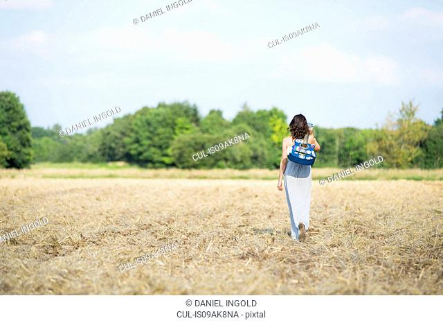 Rear view of mid adult woman strolling in field with acoustic guitar
