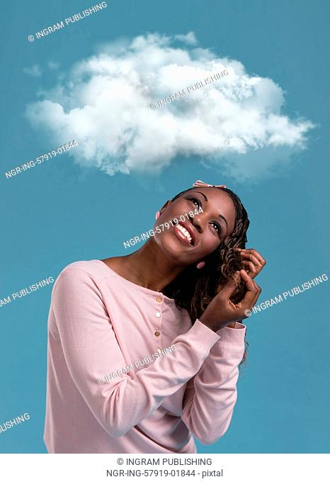 Young african woman dreaming while looking up for thought bubble above her head with copy space