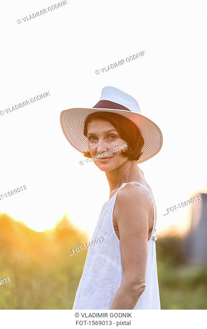 Portrait of confident woman wearing hat standing against clear sky