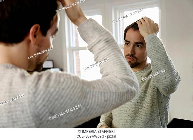 Mid adult man looking in mirror, checking hair