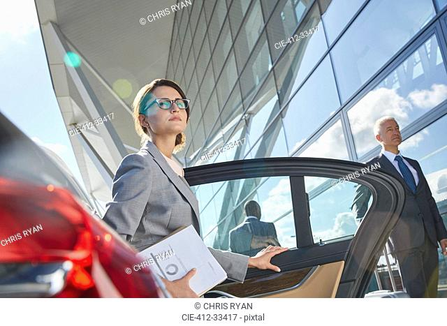 Businesswoman arriving at airport getting out of town car