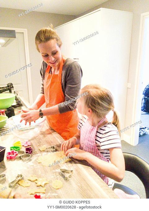 Kaatsheuvel, Netherlands. Caucasian mother and her ten year old daughter together baking cookies