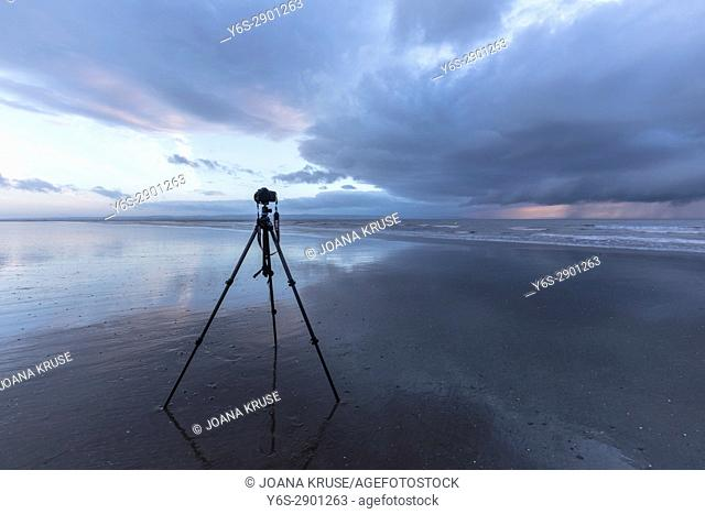camera on a tripod during low tide at the beach, waiting to capture the sunset