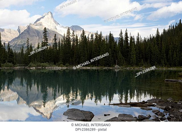 Mountain with sunlit peak reflecting in alpine lake with blue sky and clouds; British Columbia, Canada
