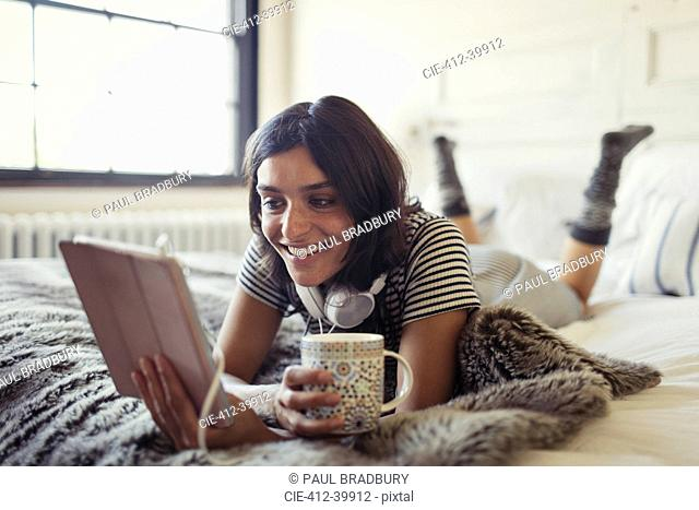 Smiling young woman drinking coffee and using digital tablet on bed