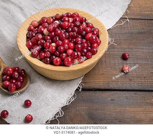 red berries of ripe lingonberries in a wooden bowl on a brown table, top view