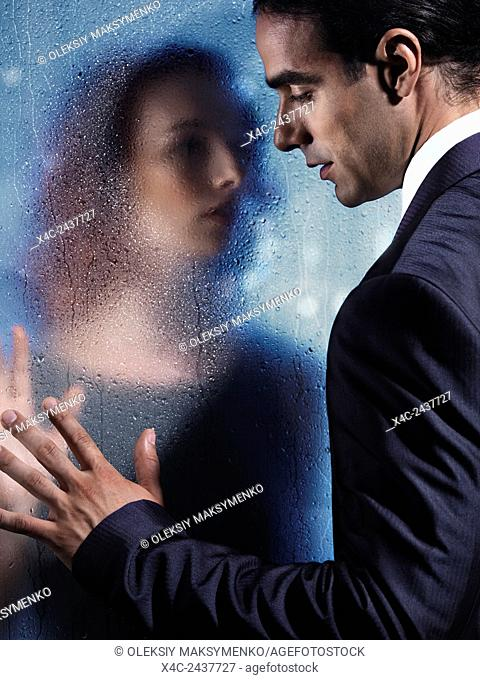 Emotional portrait of a young man and a woman separated by a wet glass pane. Couple relationship concept