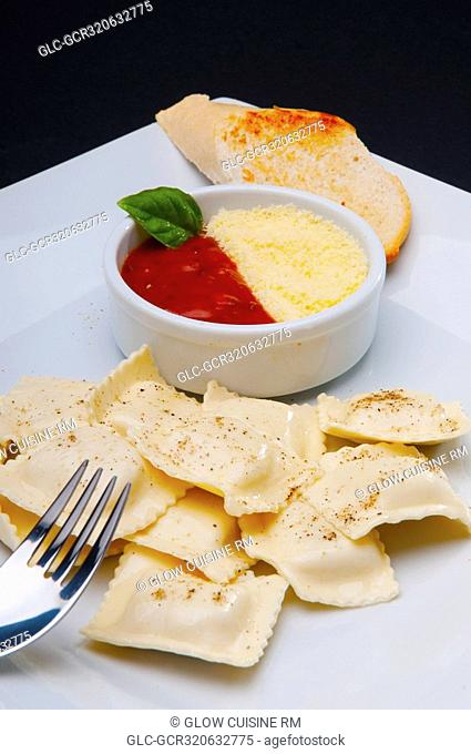 High angle view of ravioli served with tomato sauce and grated cheese