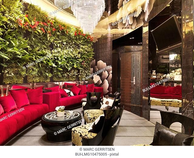 Walled red sofa with crystal chandeliers and plants in restaurant
