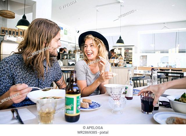 Happy male and female friends having food in restaurant